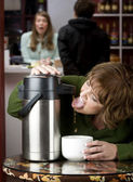 Woman drinking coffee directly from a dispenser — Stock Photo
