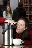 Woman drinking coffee directly from a dispenser — ストック写真
