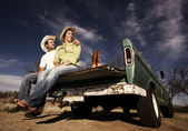 Cowboy and woman on pickup truck — Stock Photo