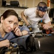 Bored woman with mechanic in background — Stock Photo