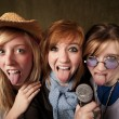 Stock Photo: Three Young Girls with Microphone and Tongues Out