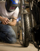 Welder working on motorcycle — Stock Photo