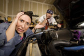 Frustrated woman with incompetent mechanic in background — Stock Photo