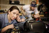 Bored woman with mechanic in background — Stockfoto