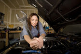 Hispanic woman in garage with wrench — Stock Photo