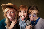 Three Young Girls with Microphone and Tongues Out — Stockfoto