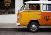 Old orange vehicle in front of hotel — Stock Photo