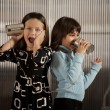 Little girl getting shocking message on tin can phone — Stockfoto