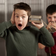 Little boy getting shocking message on tin can phone — Stockfoto