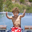 Stock Photo: Boy Splashing in Pool