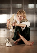 Cute young girl putting on adult shoe — Stock Photo