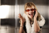 Cute young girl in red glasses talking on cell phone — Stock Photo