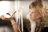 Cute young girl looking scornfully at an adult shoe — Stock Photo