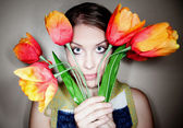 Girl Peeking Out from Behind Plastic Flowers — ストック写真