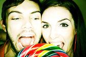 Couple Biting into Lollipop — Stock Photo