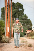 Man in camoflauge walking on dirt road — Stock Photo