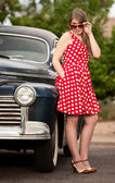 Girl in red with vintage car — Stock Photo