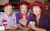 Ladies wearing red hats playing cards — Stock Photo