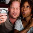 Mixed race couple in coffee house with taking picture cell phone — Stock Photo #39770439
