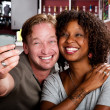 Mixed race couple in coffee house with taking picture cell phone — Stock Photo #39770445