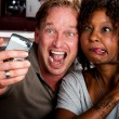 Mixed race couple in coffee house with taking picture cell phone — Stock Photo #39770457