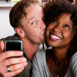 Mixed race couple in coffee house with taking picture cell phone — Stock Photo #39770505