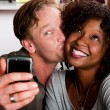 Mixed race couple in coffee house with taking picture cell phone — Stock Photo