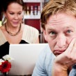 Bored man with woman on laptop computer — Stock Photo #39770985