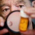 Man examining instructions on medicine bottle — Stock Photo