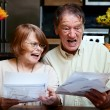 Senior couple at home with many bills — Stock Photo #39775285