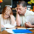 Senior couple at home with many bills — Stock Photo #39775389