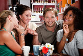 Man with three pretty women in coffee house — Stock fotografie