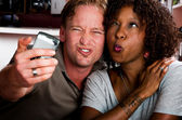Mixed race couple in coffee house with taking picture cell phone — Stock fotografie