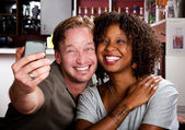 Mixed race couple in coffee house with taking picture cell phone — Foto Stock