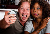 Mixed race couple in coffee house with taking picture cell phone — Zdjęcie stockowe