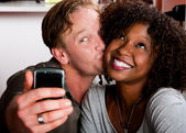 Mixed race couple in coffee house with taking picture cell phone — Stok fotoğraf