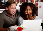 Mixed race couple in coffee house with laptop computer — Stock Photo