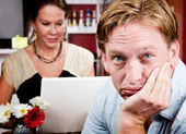 Bored man with woman on laptop computer — Stock Photo