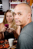 Bored man with woman on cell phone — Stockfoto