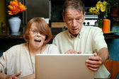 Senior couple shocked at the content on their computer — Stock Photo