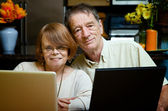 Senior couple using laptop computers at home — Stock Photo