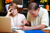 Senior couple at home with many bills — Stock Photo