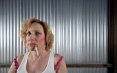 Woman smoking in front of corrugated metal — Stock Photo