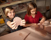 Cute young girls in a clay studio — Stock Photo
