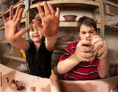 Kids with messy hands in clay studio — Stock Photo