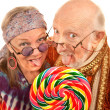 Hippie seniors licking a lollipop — Stock Photo
