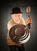 Senior defending himself with spoon and can lid — Stok fotoğraf