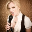 Stock Photo: Pretty young singer or comedian with microphone