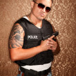 Hispanic Cop Holding Gun — Stock Photo #40101645