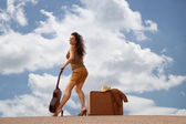 Pretty woman with suitcase and guitar — Stock Photo